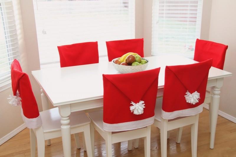 стол со стульями в чехлах-шапочках Санта-Клауса