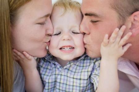 Папа и мама целующие малыша