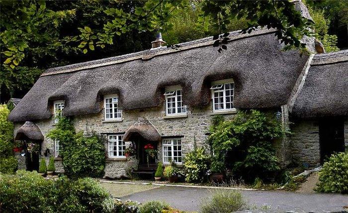 Двухэтажный дом с крышей из серой соломы
