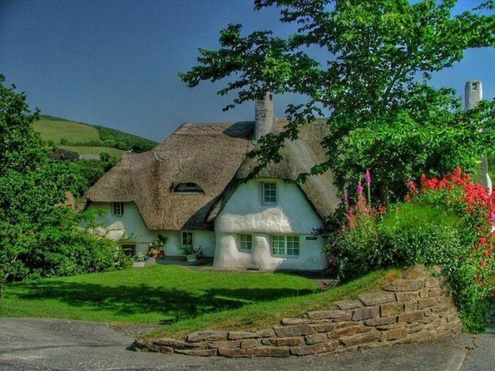 белый домик с серой соломенной крышей
