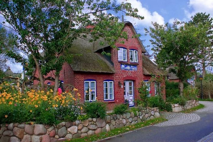 дом из красного кирпича с соломенной крышей