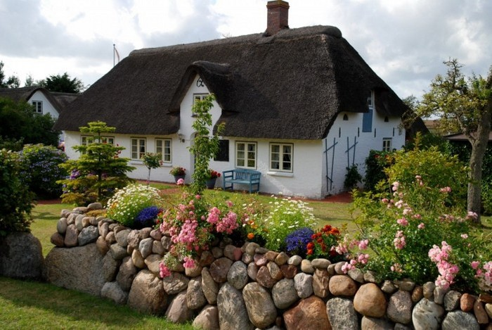 домик с соломенной крышей, цветы и каменная изгородь