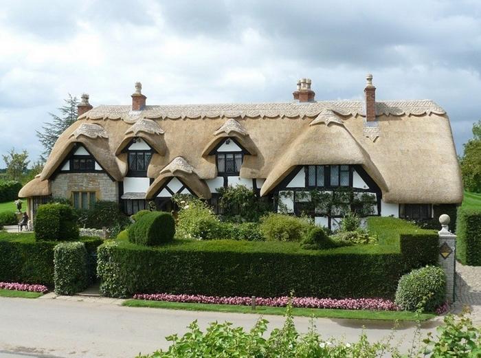 Красивый дом с светлой соломенной крышей, садом и живой изгородью